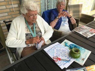 Bewoners buiten aan tafel knutselen